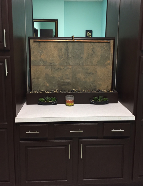Every spa needs a fountain! (And this one was a perfect solution to hide the oddly placed mirror.) The fountain uses copper, wood and other parts from our master craftsmen's home renovation projects. Old cabinets were stained a rich dark chocolate, pairing perfectly with the soothing mint green of the walls.